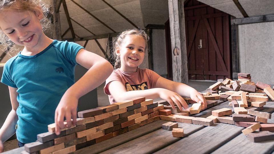 To piger leger med teglsten på Cathrinesminde Teglværk